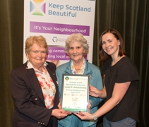 Ann Taylor and Isobel Turner accept the certificate from Katheryn Bennett
